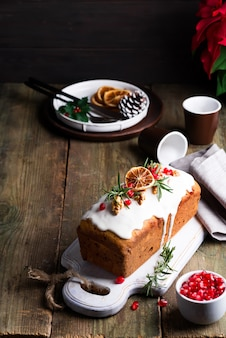Fruit cake dusted with icing, nuts, kernels pomegranate and dry orange on old wooden . christmas and winter holidays homemade cake