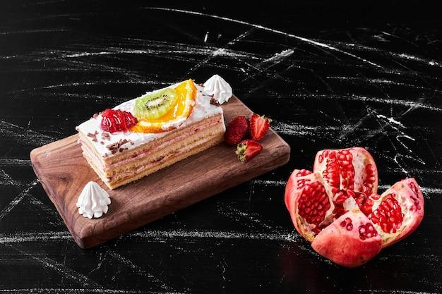 Кусок фруктового торта на деревянном блюде.