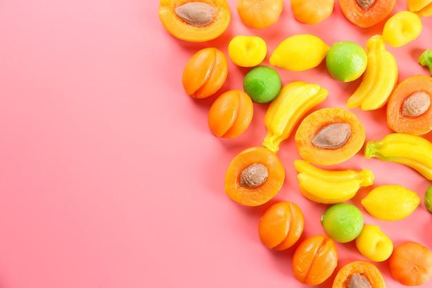 Фруктовые конфеты на розовом фоне
