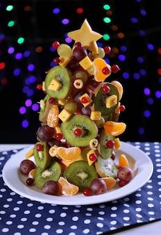 暗い背景の上のテーブルの上のフルーツのクリスマスツリー