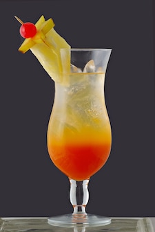 Fruit cocktail drink in glass bowl on gray background.