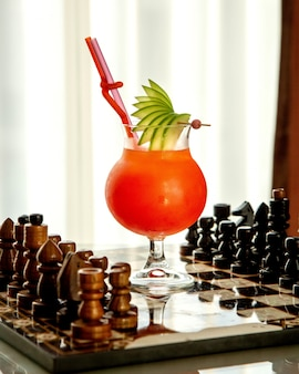 Fruit cocktail garnished with apple slices placed on chess board