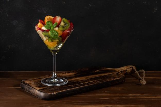 木製のテーブルの上のマティーニグラスのフルーツカクテル。