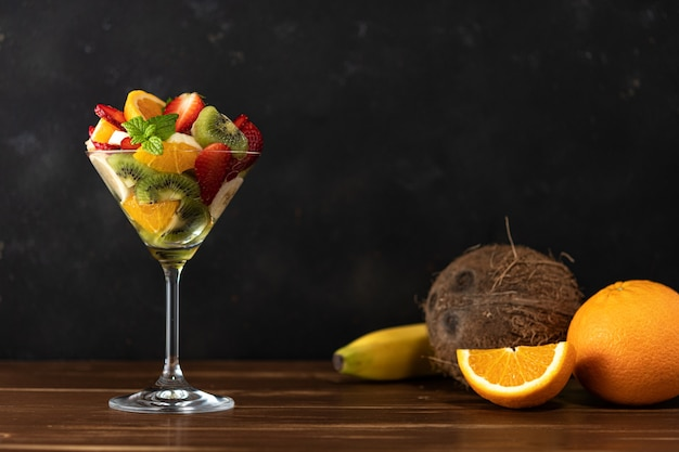 Fruit cocktail in martini glass on wooden table.