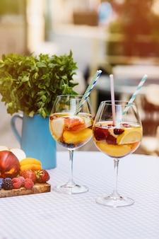 フルーツカクテルベリーとミントの葉と白い木製テーブル