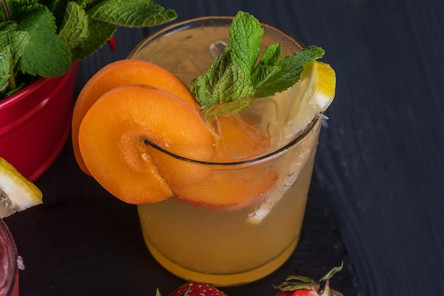 Фруктовый коктейль со свежими фруктами и льдом. в очках на деревенском черном деревянном фоне
