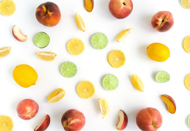 白い背景の上のレモンライムと桃のスライスのフルーツコラージュフラットレイ