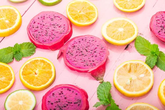 フルーツ。青い木の板にカラフルな新鮮な果物。オレンジ、ドラゴンフルーツ、レモン、フラット横たわっていた、トップビュー、