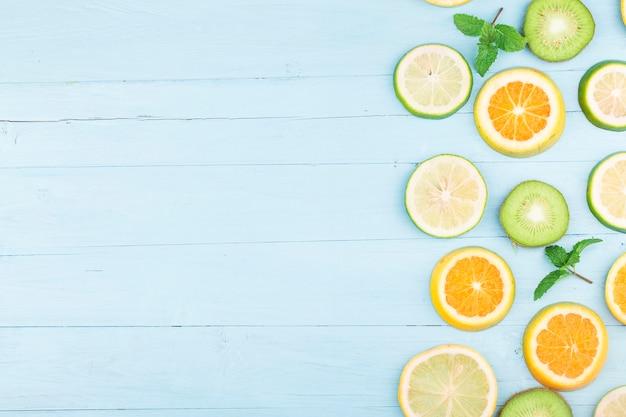 과일. 푸른 나무 보드에 다채로운 신선한 과일입니다. 오렌지, 키위, 레몬, 플랫 레이, 탑 뷰,
