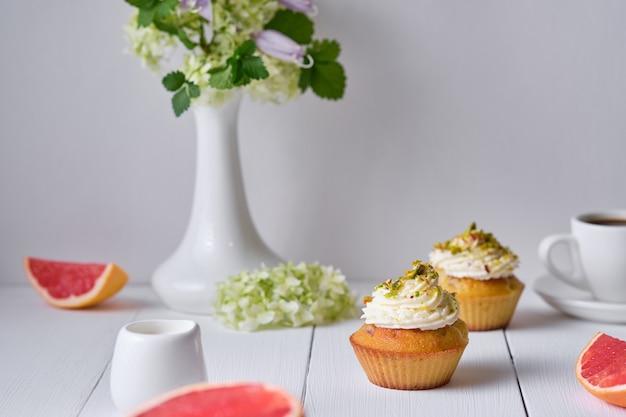 朝食用のフルーツカップケーキ。白い木製のテーブルの上に花瓶にデザート、エスプレッソ、グレープフルーツ、花と朝のテーブル。