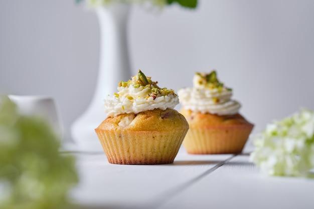 白い木製のテーブルの上に花瓶に挽いたピスタチオと花で飾られたクリームとフルーツのカップケーキ。朝、素朴な静物。