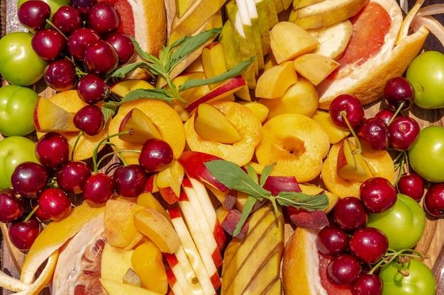 Фруктовая нарезка яблок, вишни, грейпфрута, бананов, грушевых абрикосов