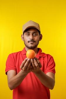 果物の配達の概念:手にオレンジ色の果物を保持しているインドの配達人