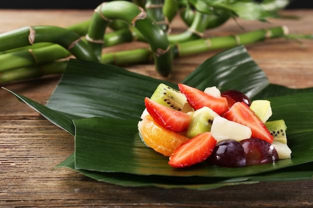 Фруктовый десерт на зеленом листе на столе