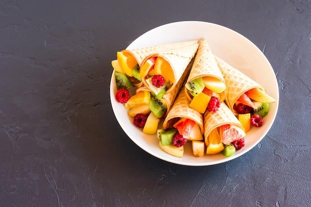 과일 디저트. 하얀 접시에 과일로 가득 찬 와플 콘. 여름의 끝자락과 달콤한 메뉴.