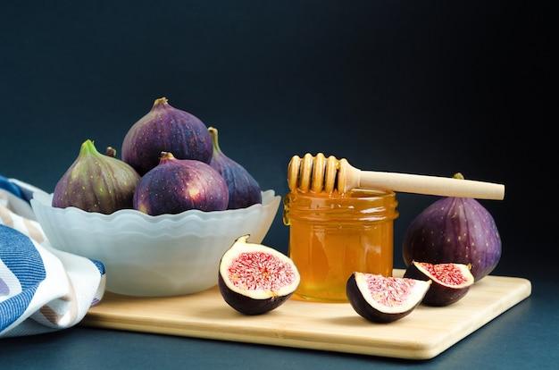 Fruit dessert with honey. ripe juicy purple figs in bowl on wooden board