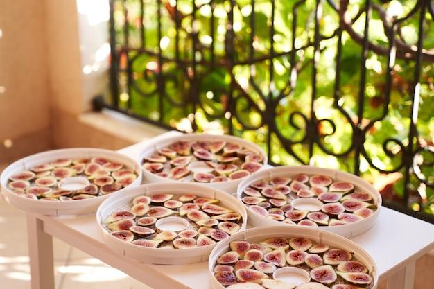 Процесс сушки фруктов на тарелках на балконном столе
