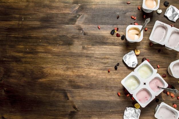 Фруктовые свежие йогурты. на деревянном столе. вид сверху