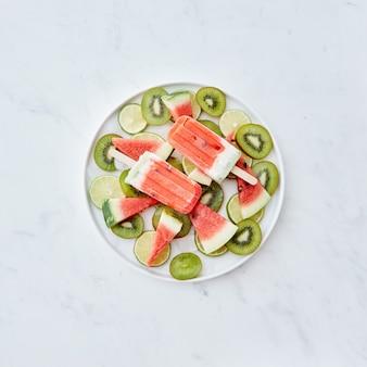 氷の入った皿にスイカのかけらの形をしたスティック上のフルーツ冷凍スムージーと、テキスト用のスペースのある灰色の壁の上のフルーツのかけら。アイスクリームキャンディー。フラットレイ