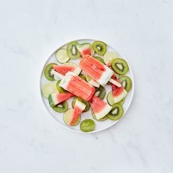 Fruit frozen smoothies on a stick in the form of a piece of watermelon in a plate with ice cubes and pieces of fruit on a gray wall with space for text . ice cream lolly. flat lay