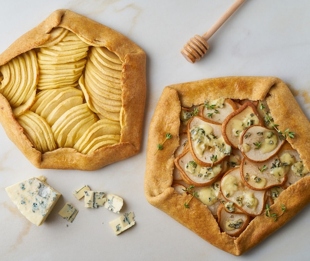 Fruit galette, apple pie with honey, savory pear and cheese pie, marble table, top view