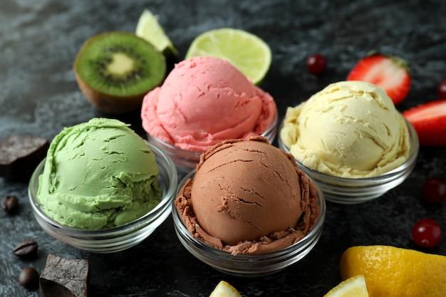 Fruit ice cream and ingredients on black smokey