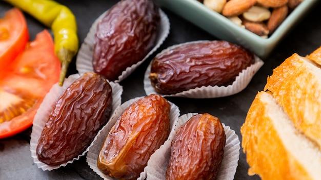 果物の画像ナツメヤシの溶接果物は甘く、健康のために砂糖を含まず、テーブルの上の美しい石の皿での食事です。
