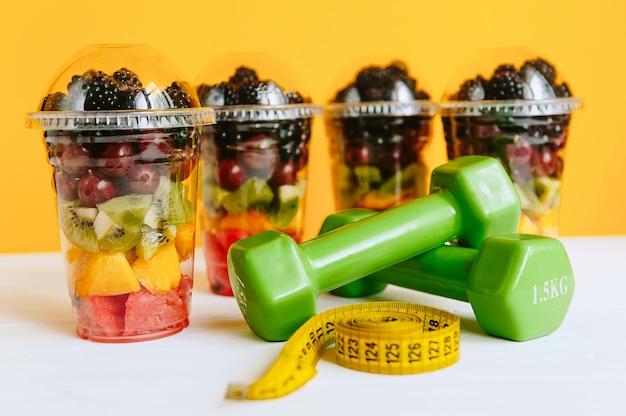 グラスに入ったフルーツ、ダンベル、体を測定するためのテープ。健康的な栄養と減量の概念