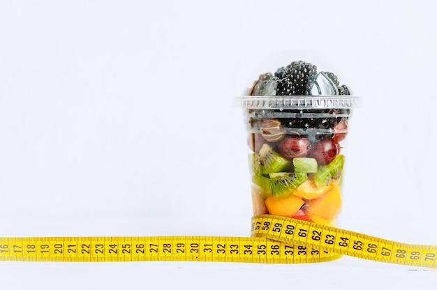 ガラスの果物、体を測定するためのテープ。健康的な栄養と減量の概念
