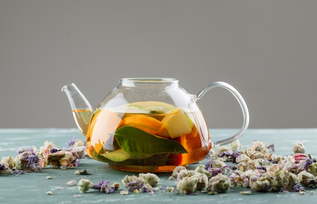 Fruit infused water in a teapot with dried flowers side view on plaster and grey surface