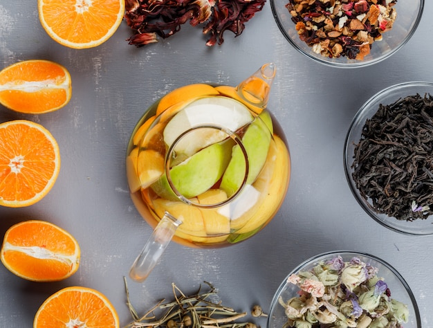 Fruit infused water in a teapot with herbs, oranges flat lay on a plaster surface