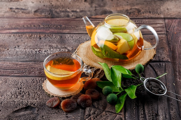 Fruit infused water in teapot with tea dried apricots, wood, container, limes high angle view on a stone tile surface