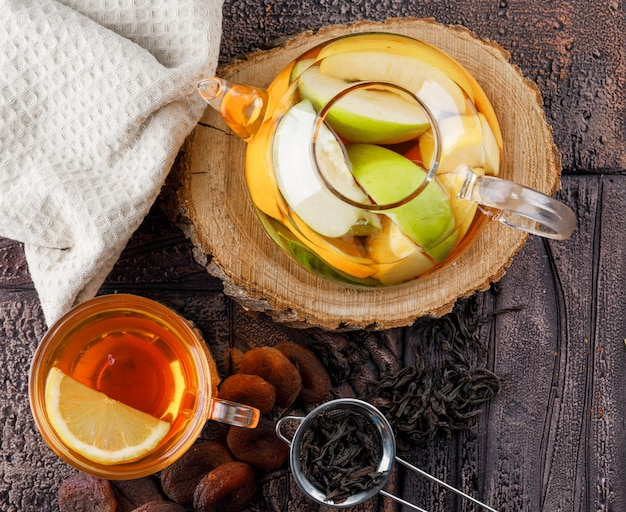 Fruit infused water in teapot with tea, dried apricots, wood, kitchen towel, container flat lay on a stone tile surface