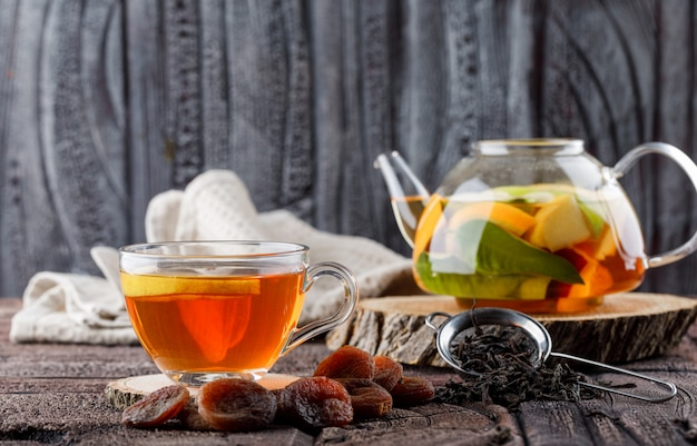 Fruit infused water in teapot with tea, dried apricots, wood, kitchen towel, container side view on stone tile and wooden surface