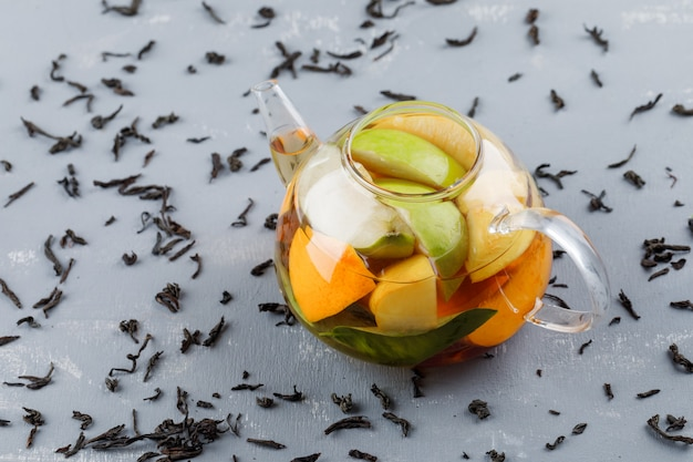 Fruit infused water with dry tea in a teapot on plaster surface