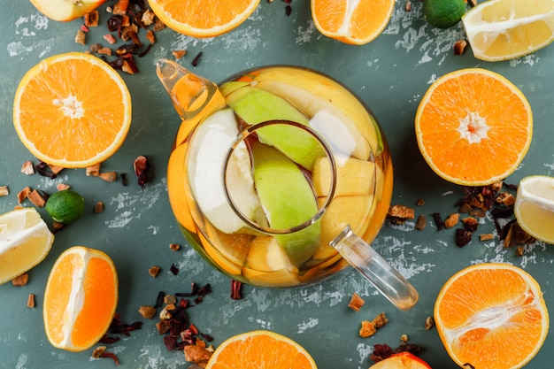 Fruit infused water with mixed dried herbs, oranges, limes in a teapot on plaster surface
