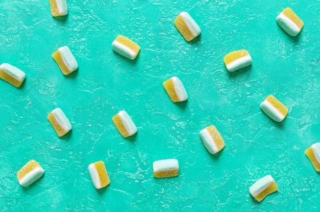Fruit jelly candies in the form of melon slices on a bright turquoise background. food background.