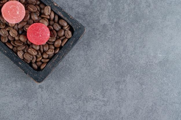 暗い板の上にコーヒー豆とフルーツゼリーキャンディー