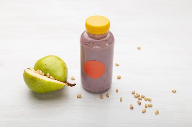 Фруктовый сок в банке рядом с кусочками груши и кедровых орехов, стоящих на белом столе. концепция здорового перекуса и обеда на работе.