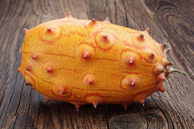 과일 키와노 - 오래된 나무 탁자에 있는 아프리카 뿔 멜론 또는 오이