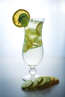 Fruit lemonade in hurricane glass with lemon and cucumber.