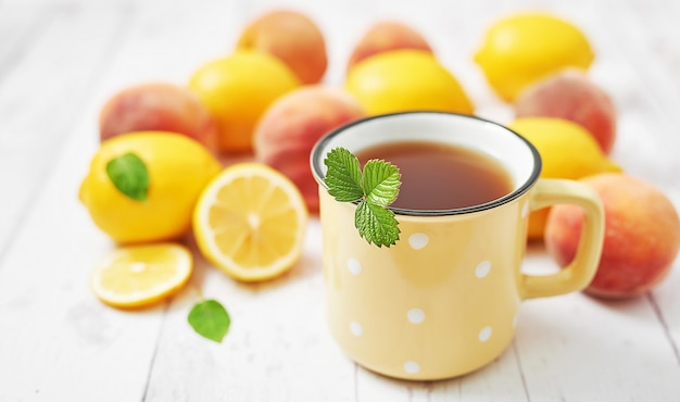 Фруктовые лимоны и персики на белом столе
