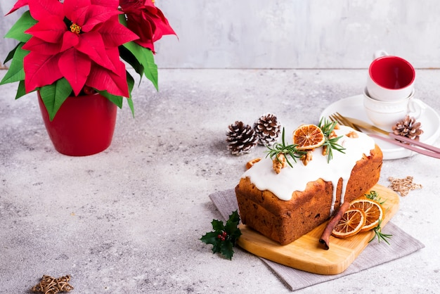 Fruit loaf cake dusted with icing, nuts and dry orange on stone . christmas and winter holidays poinsettia on