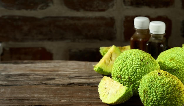 Fruit of the maclura pomifera tree or horse apple on wooden table.