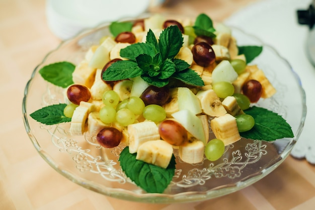 Fruit mix on plate of bananas, grapes and apple for healthy vegetarian diet