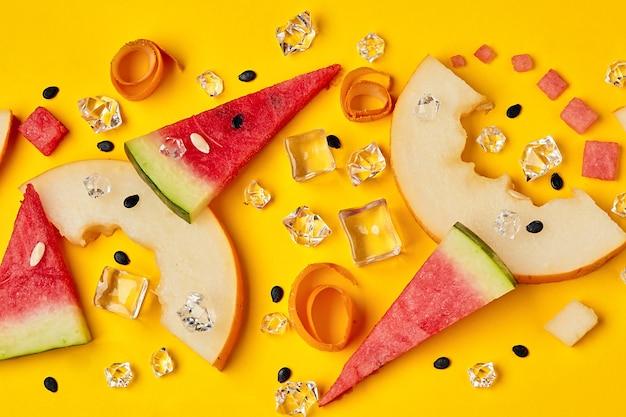 Фруктовый микс с кусочками арбуза и дыни рядом с кубиками льда на желтом фоне яркая реклама