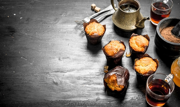 Fruit muffins with fragrant tea on black chalkboard.