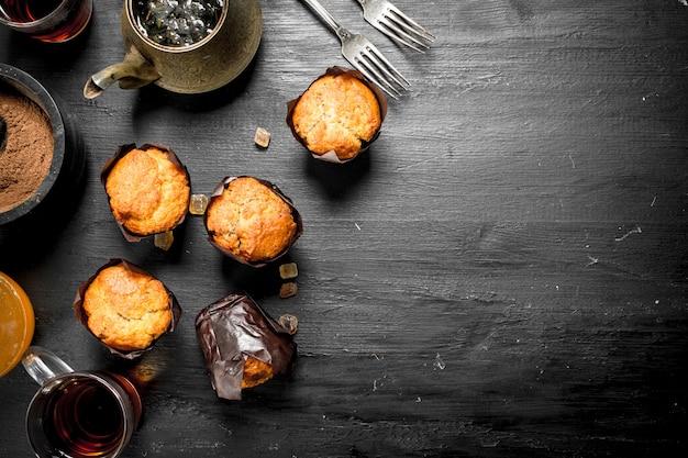 검은 칠판에 향기로운 차와 과일 머핀.