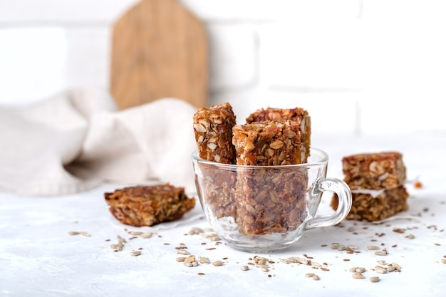Fruit nut bars in glass, transparent cup, useful components, for healthy concept. light background