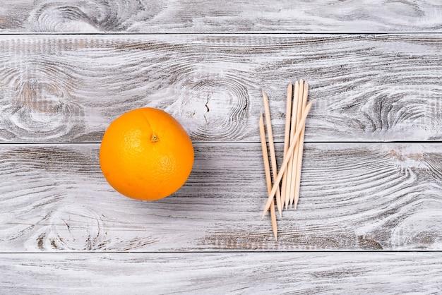 マニキュア用フルーツオレンジとオレンジウッドスティックキューティクルプッシャー。テキスト、バナーのコピースペース。